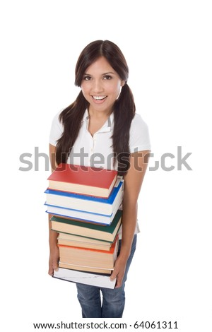 Young Hispanic female college student in jeans holding huge pile of educational books from library - stock photo