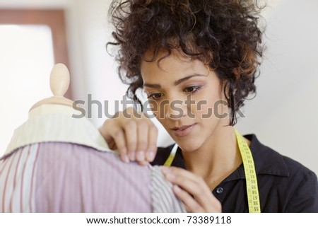 Young hispanic female dressmaker adjusting clothes on tailoring mannequin and smiling. Horizontal shape, head and shoulders