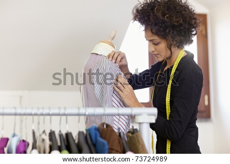 Young hispanic female dressmaker adjusting clothes on tailoring mannequin. Horizontal shape, waist up, copy space