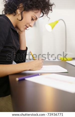 Young hispanic female dressmaker sketching and drawing new dresses and models. Vertical shape, side view, copy space - stock photo