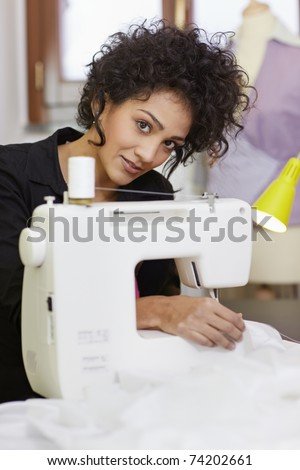 Young hispanic female dressmaker using sewing machine and smiling at camera. Vertical shape, side view, waist up - stock photo