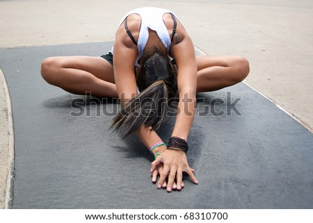 young hispanic female stretching outside before a run - stock photo