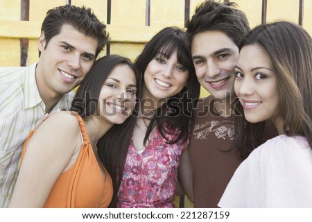 Young Hispanic friends hugging - stock photo