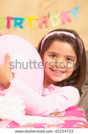 Young Hispanic girl with large gift and balloon - stock photo