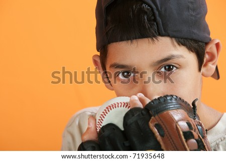 Young Hispanic male with baseball, mitt and backwards hat - stock photo