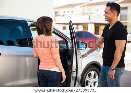 Young Hispanic man being a gentleman and opening the car door for her date - stock photo