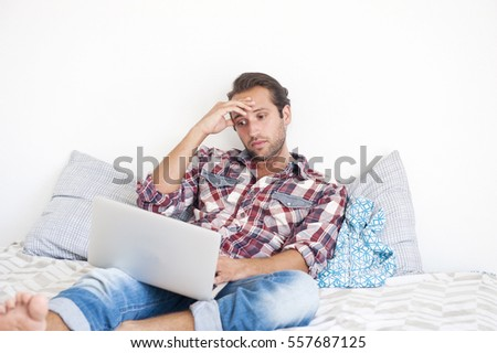 Young Hispanic Man on Bed with Computer