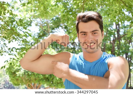 Young hispanic man showing his arm biceps muscles. Fitness mal at the park. - stock photo