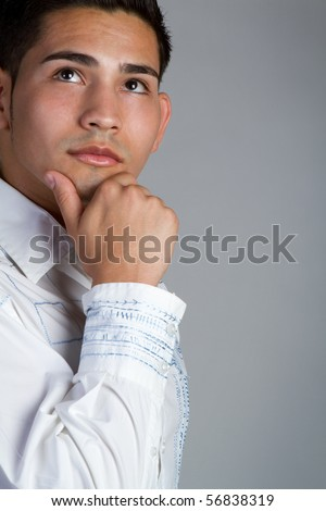 Young hispanic man thinking - stock photo