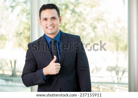 Young Hispanic man wearing a suit and giving his approval with a thumb up - stock photo