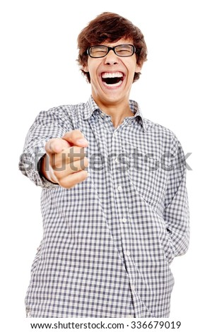 Young hispanic man wearing blue checkered shirt and black glasses pointing at camera with his index finger and laughing out loud isolated on white background - humor concept - stock photo