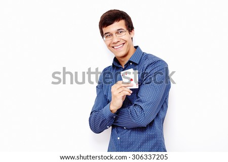 Young hispanic man wearing blue shirt and glasses smiling and holding two aces (diamonds and hearts) in his hand against white wall - gambling concept
