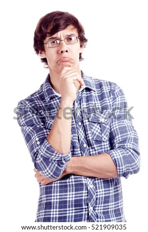 Young hispanic man wearing glasses and blue shirt with rolled up sleeves standing with hand on his chin and looking at camera with skeptical face expression isolated on white background