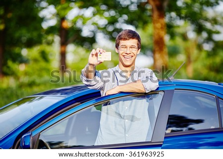 Young hispanic man wearing glasses and jeans shirt holding out his driving license and laughing against blue car outdoors - new drivers concept - stock photo