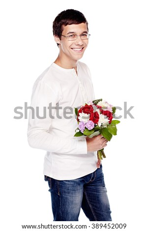 Young hispanic man wearing glasses, blue jeans and white long sleeve, standing with bunch of flowers in his hands and smiling - dating concept