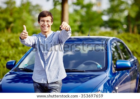 Young hispanic man wearing glasses holding out car keys, showing thumb up hand gesture and smiling against blue car outdoors - new drivers concept - stock photo
