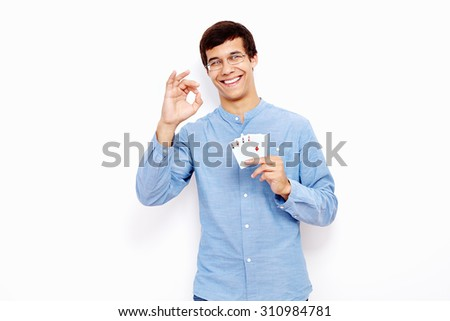 Young hispanic man wearing jeans and glasses holding four aces (spades, hearts, clubs and diamonds) in his hand and showing A-ok hand gesture with smile against white wall - gambling concept - stock photo