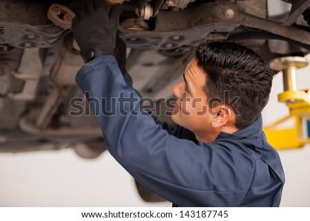 Young Hispanic mechanic fixing a car at an auto shop - stock photo