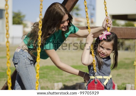 Young hispanic mother pushing daughter on the swing - stock photo