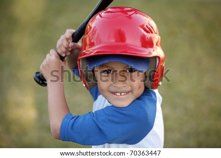 Young hispanic or latino boy with red baseball helmet over a blue hat and blue tee shirt.