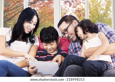 Young hispanic parents with their children using digital tablet at home with autumn background on the window - stock photo