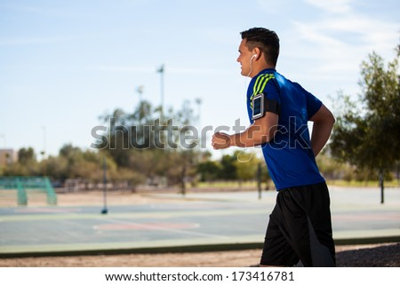Young Hispanic runner wearing and armband and listening to music while he trains - stock photo