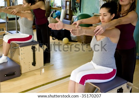 Young hispanic woman and her trainer doing pilates in a gym - stock photo