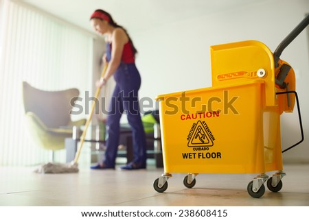Young hispanic woman at home, doing chores and housekeeping, wiping floor with water in living room - stock photo