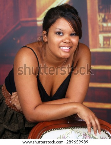 Young Hispanic woman leaning on the back of a chair.