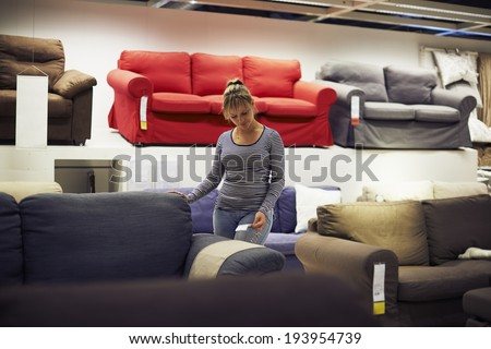 young hispanic woman shopping for furniture, sofa and home decor in store - stock photo