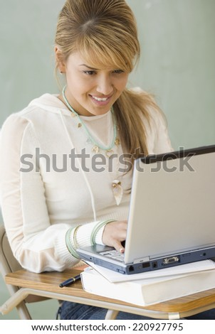 Young Hispanic woman typing on laptop - stock photo