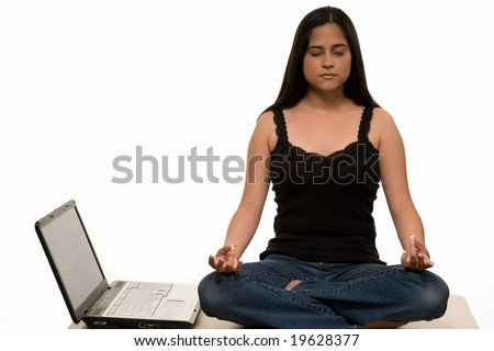 Young Hispanic woman wearing jeans and black tank top sitting in yoga pose lotus position on top of desk beside laptop computer - stock photo