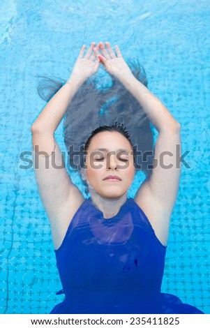 Young hispanic woman with long black  hair, floating back in the blue swimming pool - stock photo