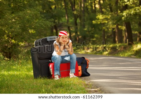 Young hitch-hiker girl standing on road side afternoon with bags - stock photo