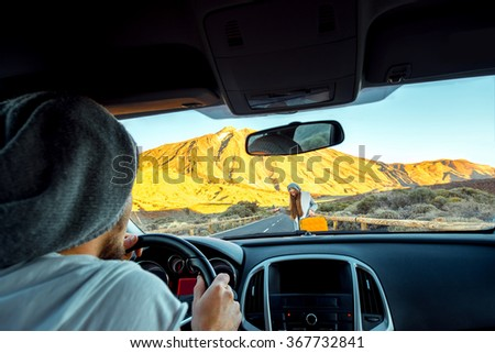 Young hitchhiker on the road and man driving - stock photo
