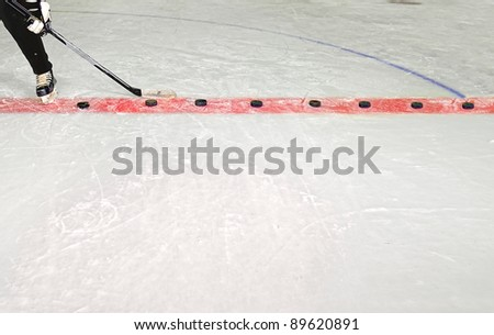 Young Hockey Player Practices Shooting Pucks with stick in Hockey Rink