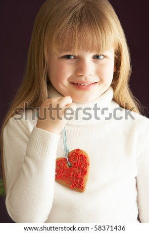 Young Holding Heart Shaped Cookie In Studio - stock photo