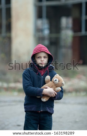 young homeless boy on the street with bear - stock photo