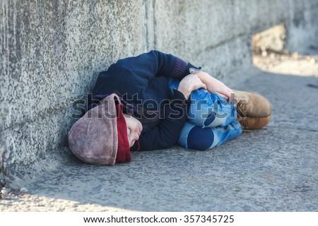 young homeless boy sleeping on the bridge, poverty, city, street - stock photo