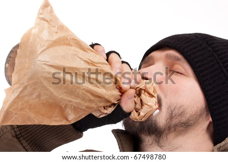 Young homeless man drinking booze from a paper bag - stock photo