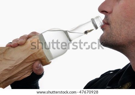Young homeless man is holding a bottle of vodka and drinking - stock photo