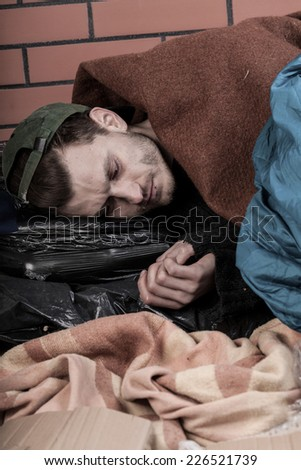 Young homeless man is stoned in the street