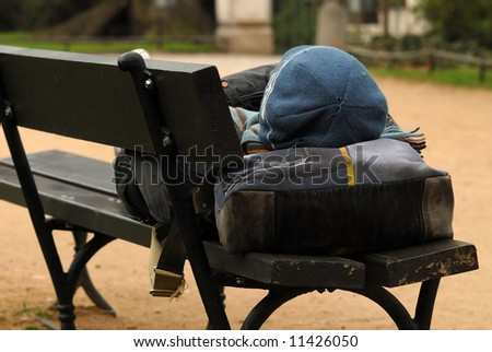 Young homeless man sleeping in the park