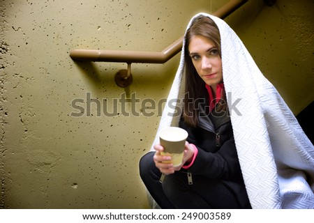 Young homeless woman sitting in a stairwell begging.   - stock photo