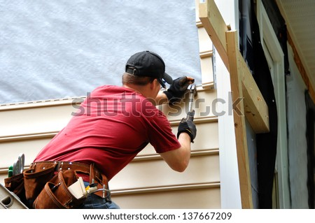 Young homeowner installs siding to his home.  He is holding a hammer and wearing a tool belt. - stock photo