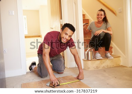 Young homeowners decorating their house, looking to camera - stock photo