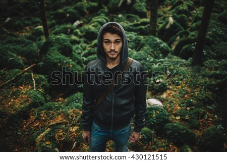 Young hooded cool man in the woods, rocks and trees on background - stock photo