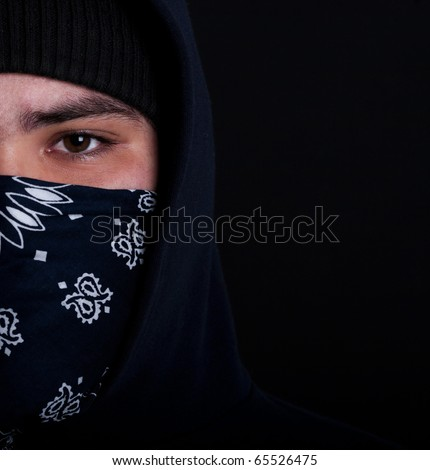 Young hooligan on dark background - stock photo