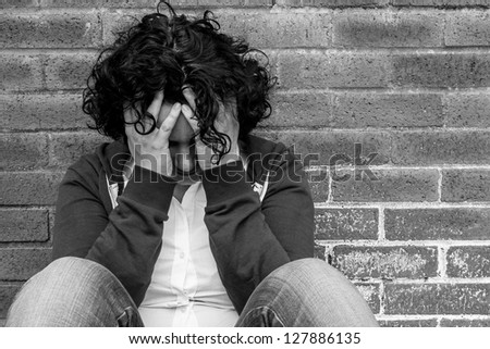 Young hopeless woman sitting against wall - stock photo