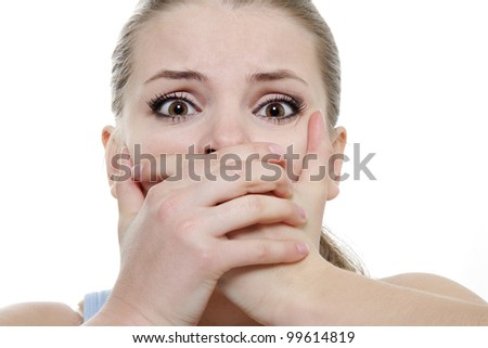 young horrified woman closing her mouth with hands over white - stock photo
